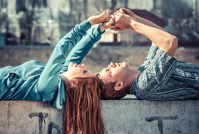 Ein Liebespaar hält sich an den Händen, während es auf einer Betonwand mit den Köpfen zueinander liegt.