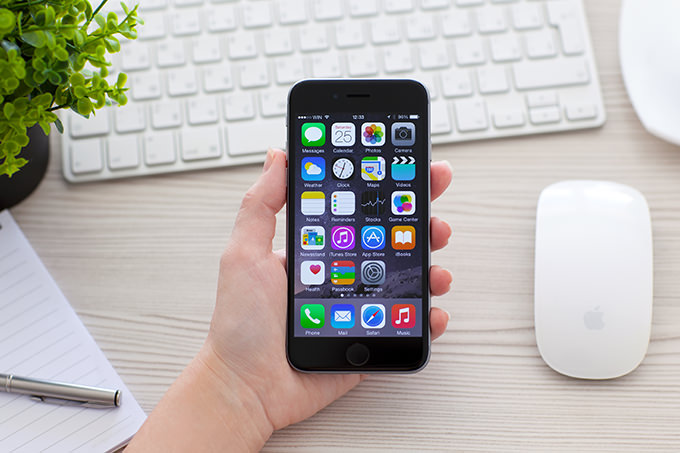 Hier wird ein iPhone 6 gezeigt. Die Person, die es hält sitzt an einem Schreibtisch.